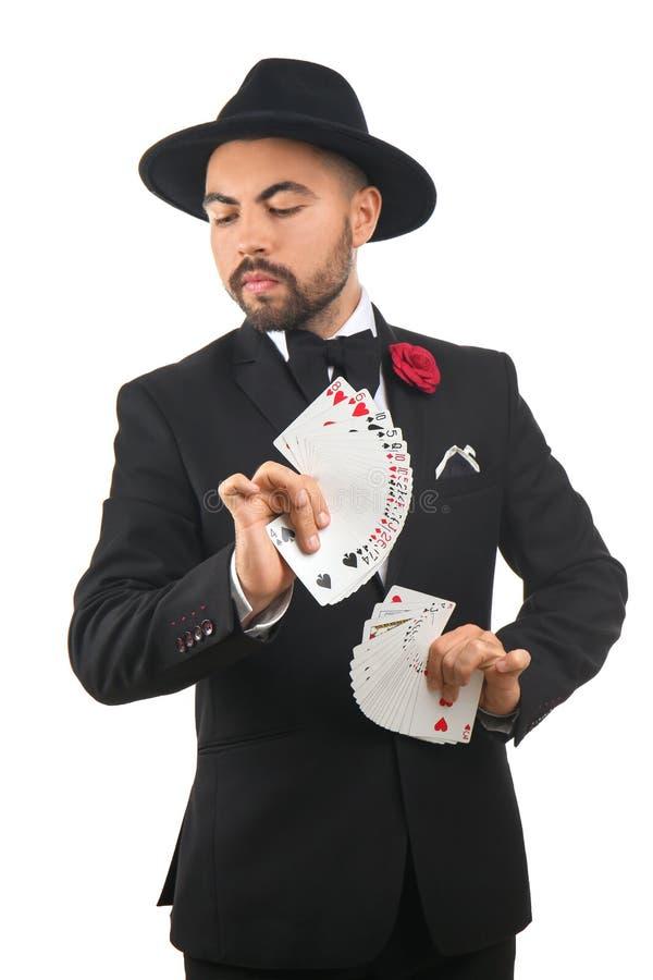 Mannelijke tovenaar die trucs met kaarten op witte achtergrond tonen royalty-vrije stock afbeeldingen