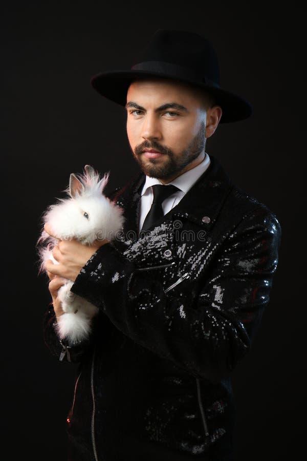 Mannelijke tovenaar met wit konijn op donkere achtergrond royalty-vrije stock foto