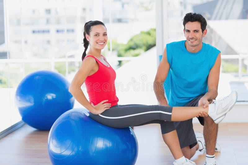 Mannelijke trainer die vrouw met haar oefeningen helpen bij gymnastiek royalty-vrije stock foto