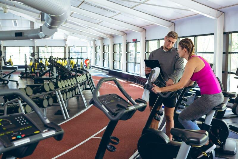 Mannelijke trainer die vrouwelijke atletisch bijstaan om op hometrainer uit te werken royalty-vrije stock afbeelding