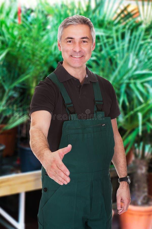 Mannelijke tuinman die zijn hand uitbreiden tot schok royalty-vrije stock afbeeldingen