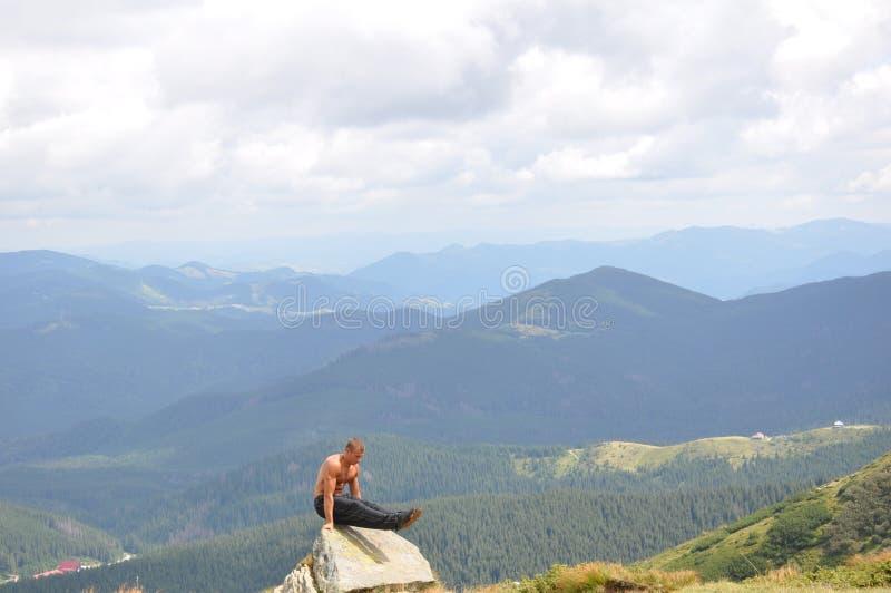 Mannelijke turner die gymnastiek- oefening in de bergen doen stock foto's