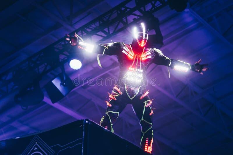 Mannelijke uitvoerder die een wit en rood geleid kostuum dragen die zich op een hoog platform bij een overleg van DJ bevinden royalty-vrije stock afbeeldingen