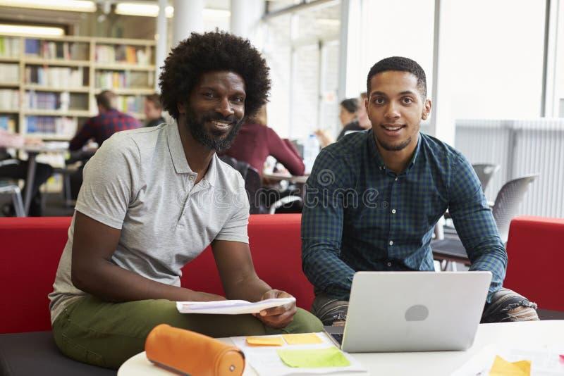 Mannelijke Universitaire Student Working In Library met Privé-leraar royalty-vrije stock fotografie