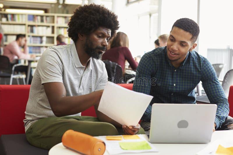 Mannelijke Universitaire Student Working In Library met Privé-leraar royalty-vrije stock foto