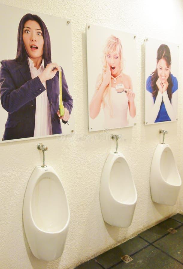 Mannelijke Urinoirs met affiche van dames het kijken stock afbeeldingen