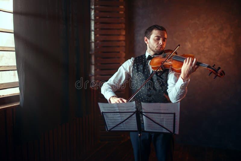 Mannelijke violist die klassieke muziek op viool spelen stock afbeeldingen