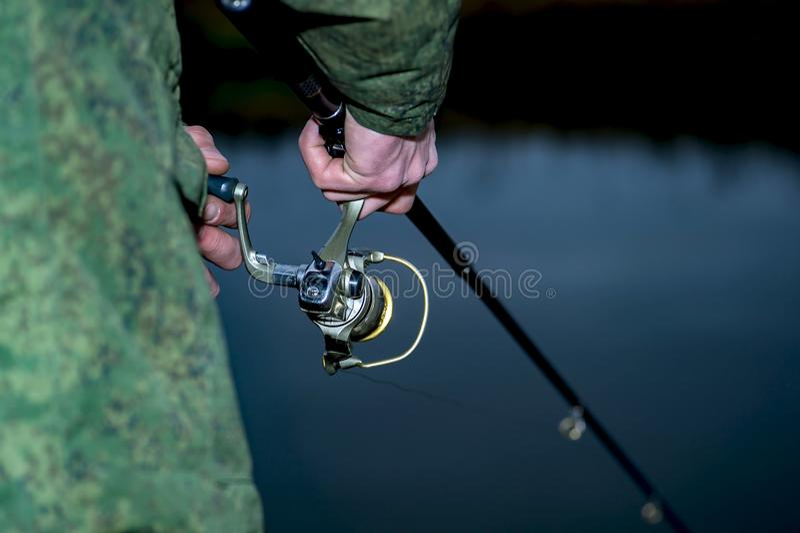Mannelijke vissersvangsten op een het spinnen vis in koud water in buiten het seizoen stock foto