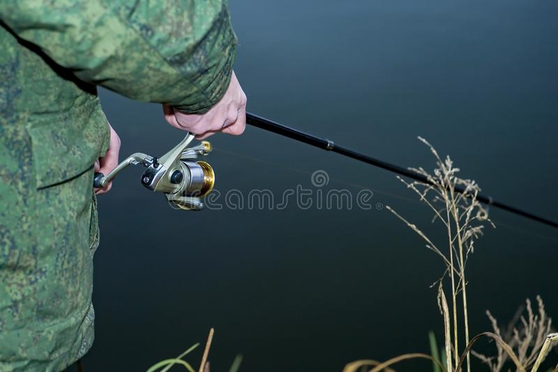 Mannelijke vissersvangsten op een het spinnen vis in koud water in buiten het seizoen royalty-vrije stock afbeelding