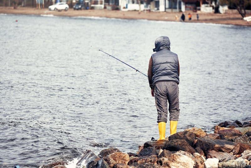 Mannelijke vissersvisser die dichtbij de kust vissen stock foto