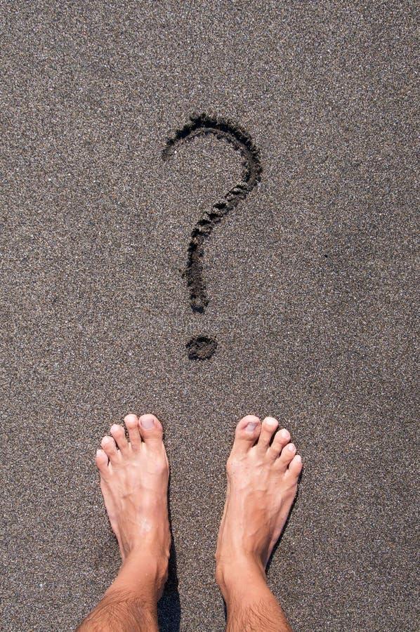 Mannelijke voeten die zich voor een vraagteken bevinden royalty-vrije stock afbeelding