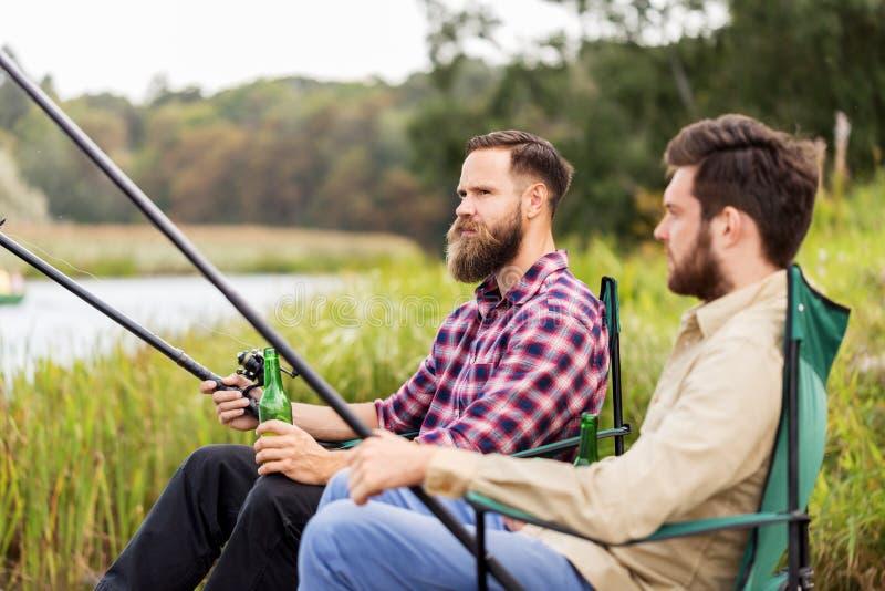 Mannelijke vrienden die en bier op meer vissen drinken stock afbeelding