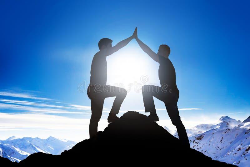 Mannelijke Vrienden die Hoogte Vijf op Bergpiek geven stock afbeeldingen