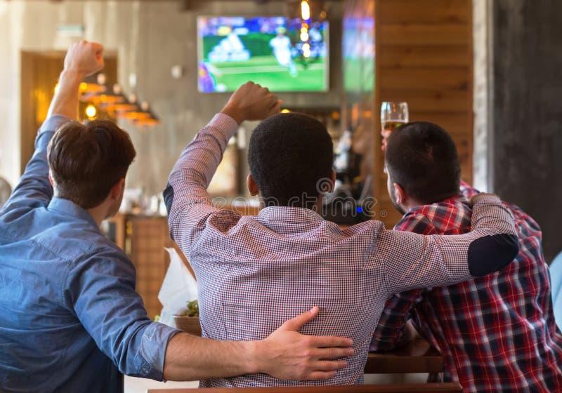 Mannelijke vrienden die op voetbalwedstrijd op TV in bar letten stock fotografie