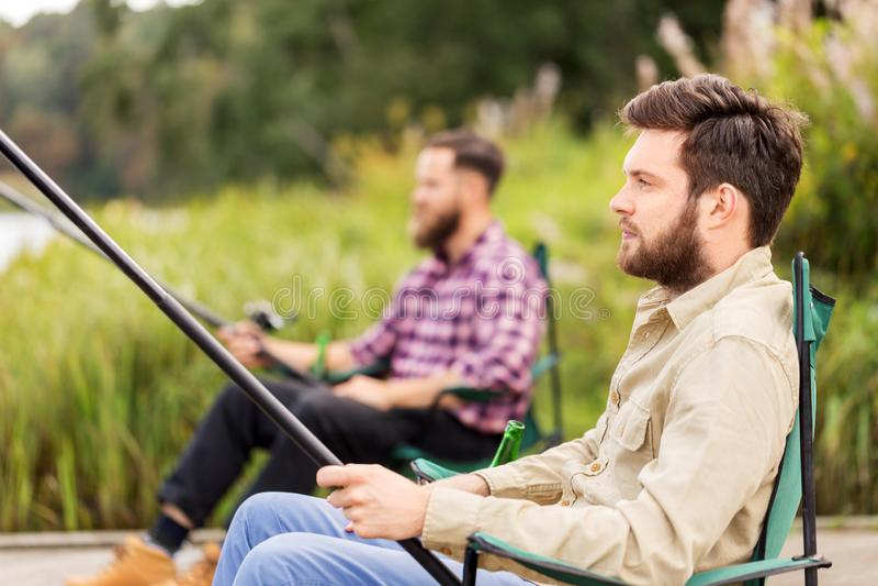 Mannelijke vrienden met hengels op meer royalty-vrije stock afbeeldingen