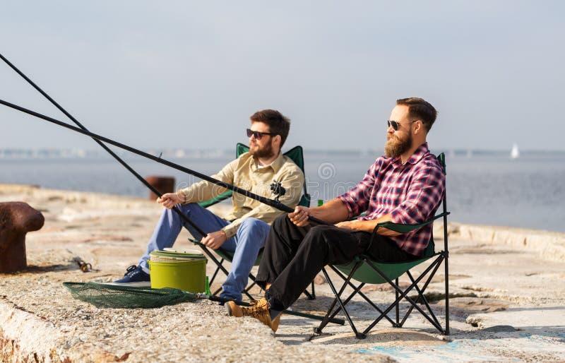 Mannelijke vrienden met hengels op overzeese pijler stock foto
