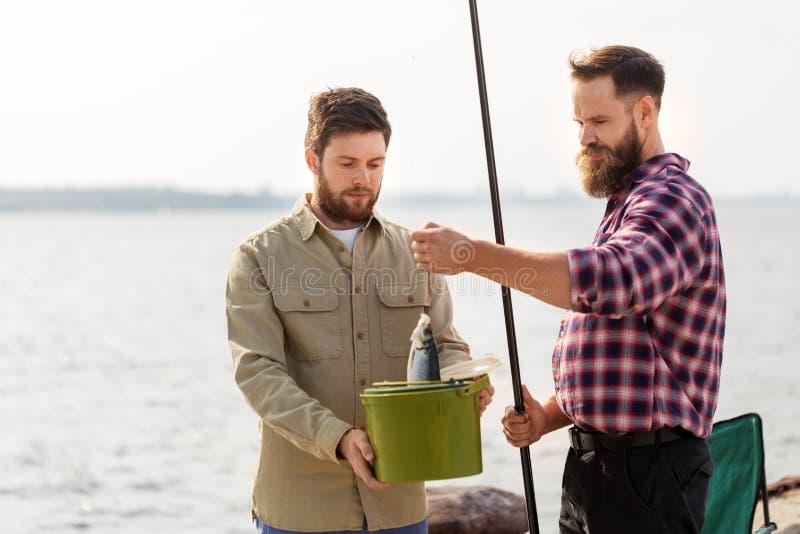 Mannelijke vrienden met vissen en hengels op pijler stock afbeeldingen