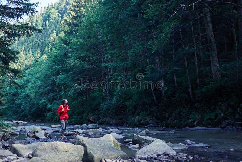 Mannelijke wandelaar die met rugzak langs bergrivier lopen stock foto's