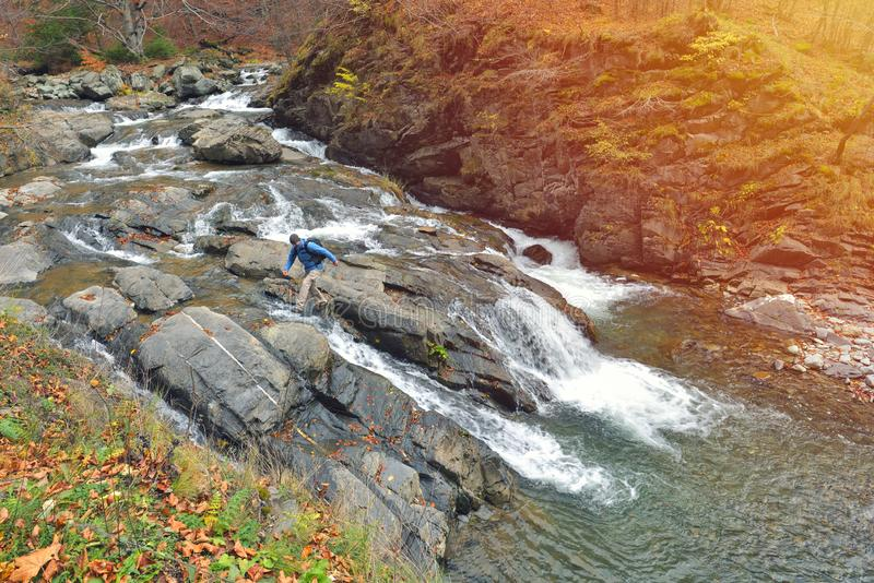 Mannelijke wandelaar die met rugzak op rotsen en waterval in fores lopen royalty-vrije stock foto's