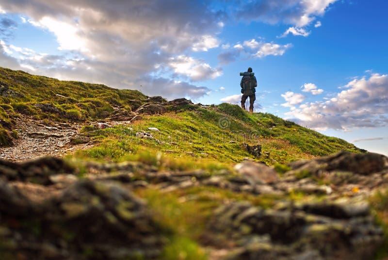 Mannelijke wandelaar die zich in hoge piek bevinden stock fotografie
