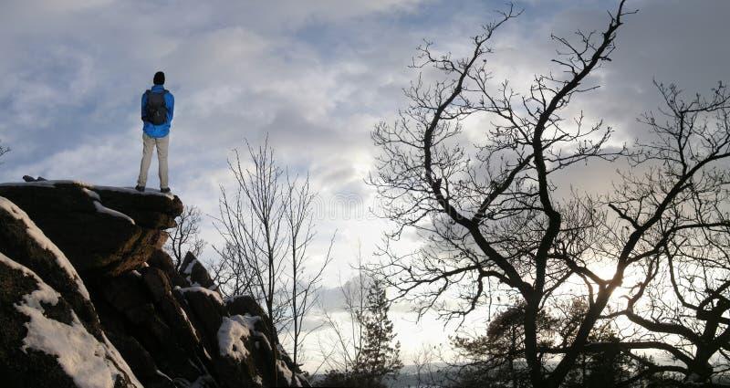 Mannelijke wandelaar met rugzak op een bergketenklip achter een stad die ruw de winterlandschap bekijken die van weekend genieten stock fotografie