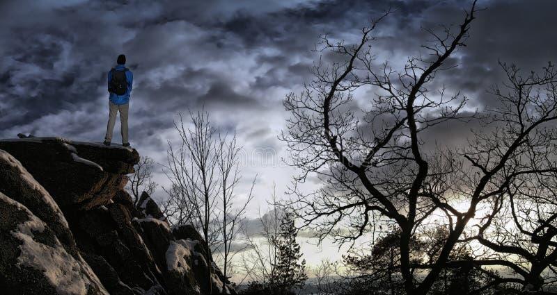 Mannelijke wandelaar met rugzak op een bergketenklip achter een stad die ruw de winterlandschap bekijken die van weekend genieten royalty-vrije stock afbeelding