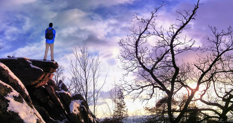 Mannelijke wandelaar met rugzak op een bergketenklip achter een stad die ruw de winterlandschap bekijken die van weekend genieten royalty-vrije stock foto's