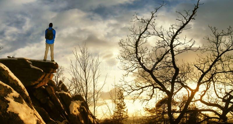 Mannelijke wandelaar met rugzak op een bergketenklip achter een stad die ruw de winterlandschap bekijken die van weekend genieten stock foto