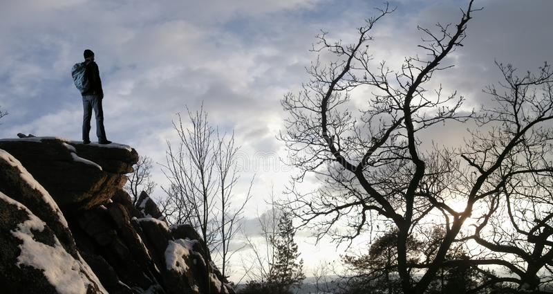 Mannelijke wandelaar met rugzak op een bergketenklip achter een stad die ruw de winterlandschap bekijken die van weekend genieten stock foto's