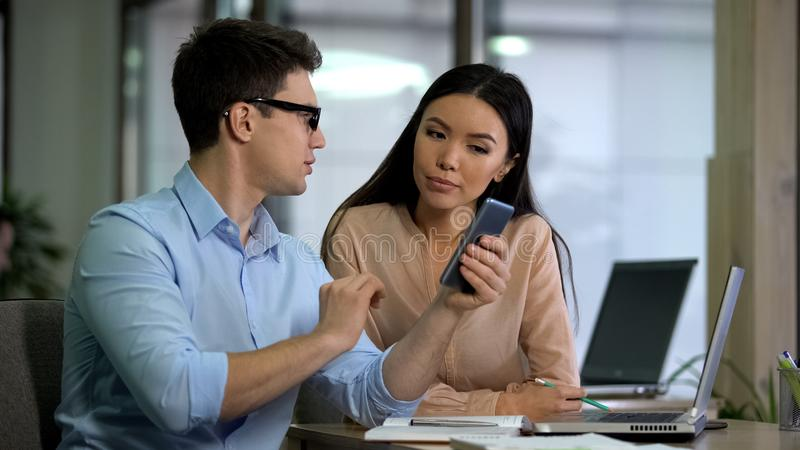 Mannelijke werknemer die aantrekkelijke Aziatische collega tonen hoe te om het dateren van app op telefoon te gebruiken stock fotografie
