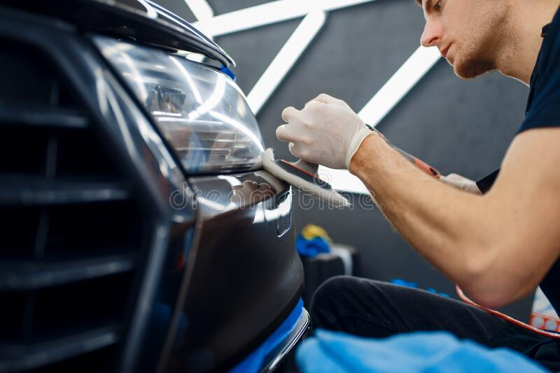 Mannelijke werknemers poetsen voorbumper, auto met details royalty-vrije stock afbeeldingen