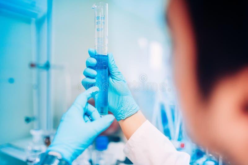 Mannelijke Wetenschapper die in laboratorium werken, vloeibare substanties vergelijken en steekproeven testen royalty-vrije stock afbeelding