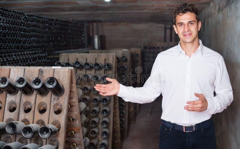 Mannelijke wijnmaker die flessen op wijnmakerij tonen stock afbeelding