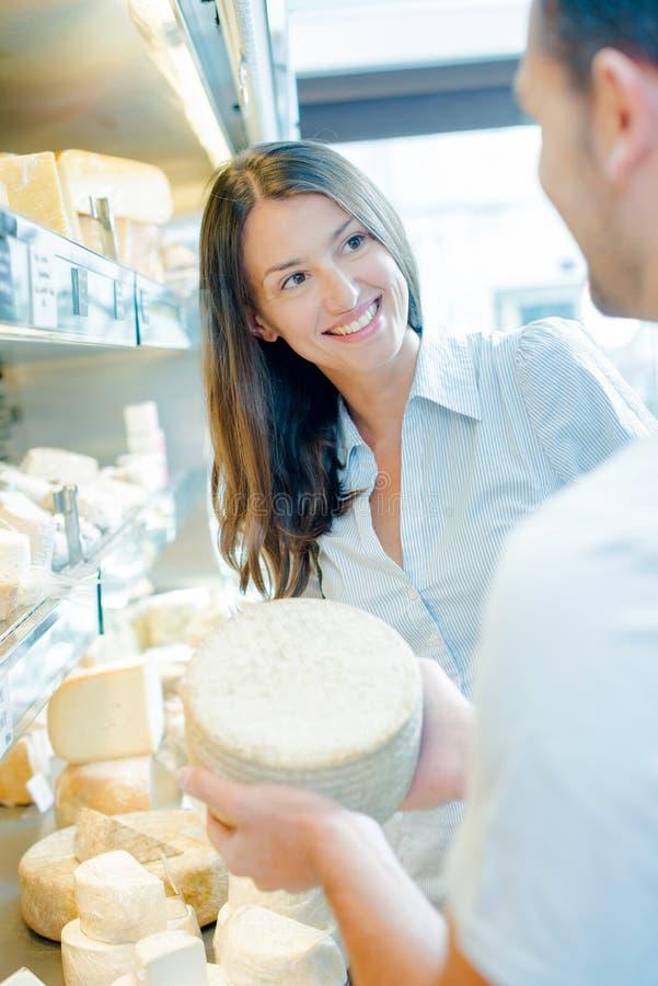 Mannelijke winkelarbeider die gehele kaas tonen aan klant stock afbeeldingen