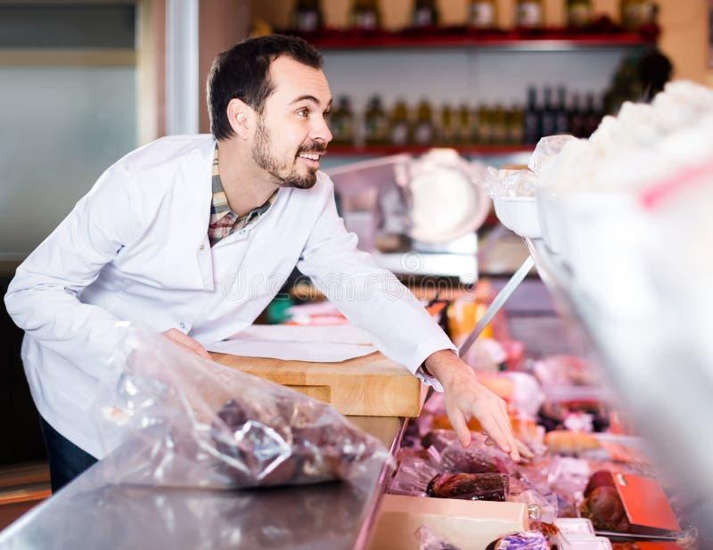 Mannelijke winkelmedewerker die gesneden bacon in sh butcher's aantonen royalty-vrije stock afbeeldingen