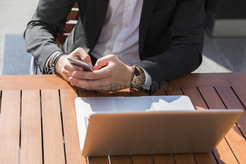 Mannelijke zakenman of arbeider die in zwart kostuum dichtbij laptop in zijn telefoon kijken royalty-vrije stock fotografie