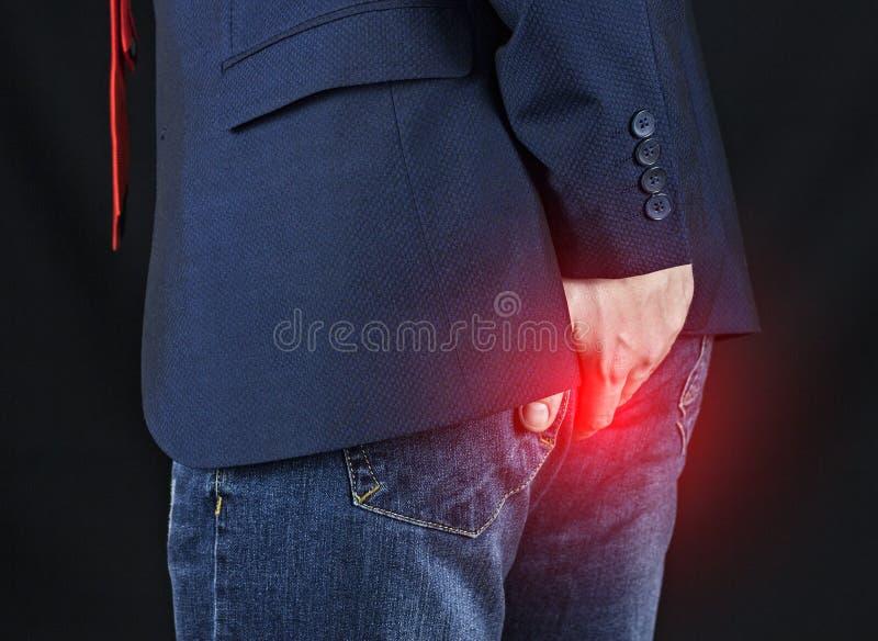 Mannelijke zakenman die zijn ezel, hemorroïden houden stock fotografie