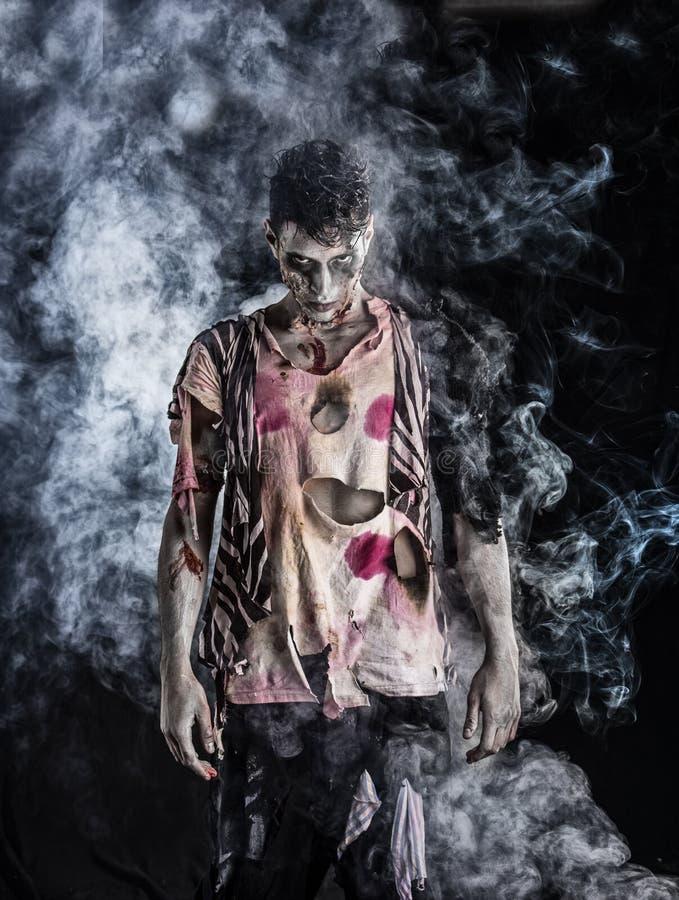 Mannelijke zombie die zich op zwarte blackground bevinden stock foto's
