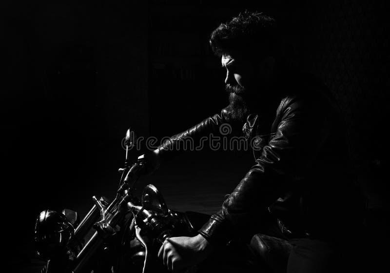 Mannelijkheidconcept Mens met baard, fietser in de zitting van het leerjasje op motorfiets in duisternis, zwarte achtergrond mach stock afbeeldingen
