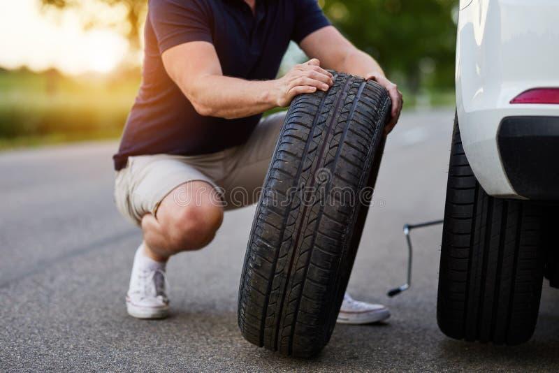Mannen ändrar gummihjulet till en bruten bil royaltyfria bilder