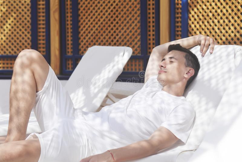 Mannen är avslappnande efter en brunnsort Mannen efter massagen En man vilar i en massage efter ett bad En man ligger på en dagdr fotografering för bildbyråer