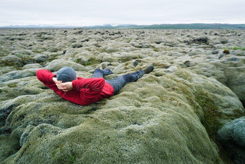 Mannen är en handelsresande på mossa på ett lavafält i Island royaltyfri fotografi