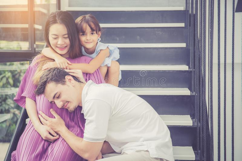 Mannen är lyssnar gravid av fru, tar förväntar den asiatiska stiliga fadern den omsorgmodern och ungen med par och att moderskap  arkivfoto