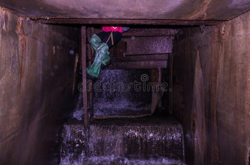 Mannen är underjordisk trappa för contrejourlightingman En person väljs från källaren royaltyfri foto