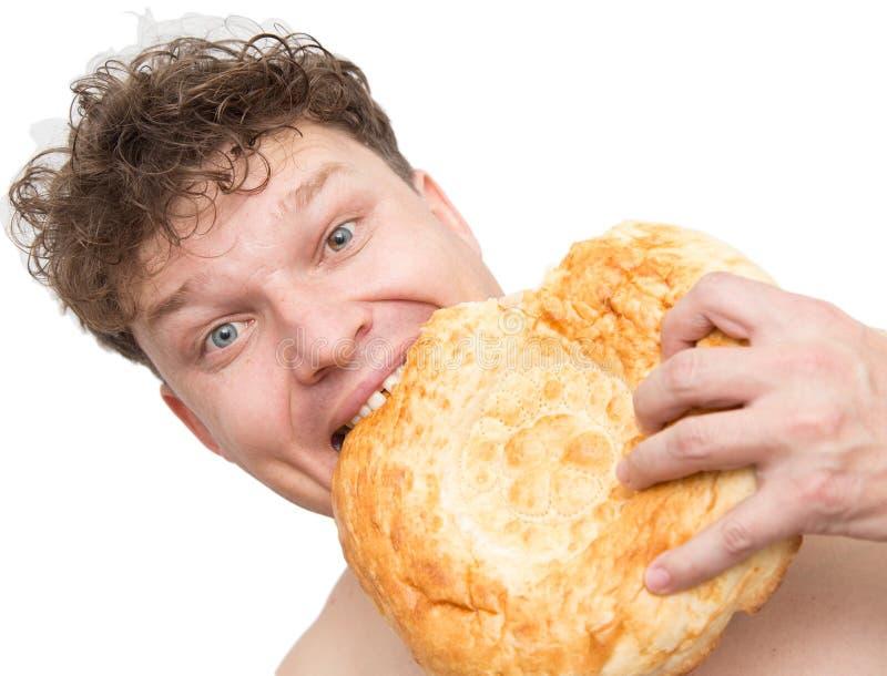 Mannen äter bröd på en vit bakgrund arkivbilder