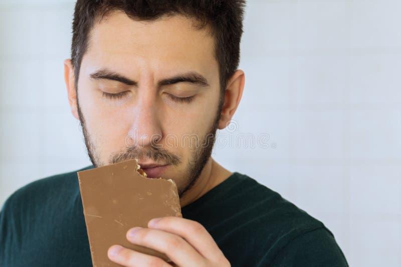 Mannen äter choklad med stort nöje arkivbild