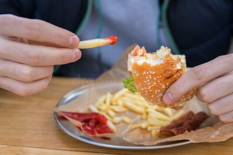 Mannen äter en hamburgare i en snabbmatgatamatställe royaltyfria foton