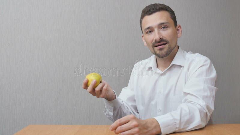 Mannen äter ett äpple arkivfoton