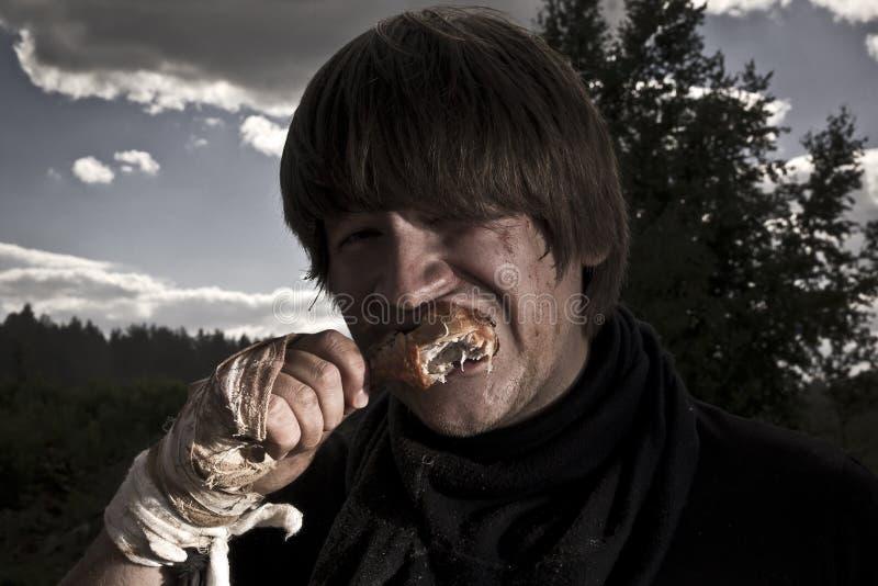 Mannen äter kött royaltyfri foto