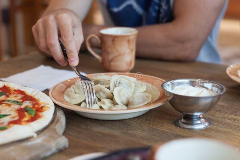Mannen äter köttklimpar i restaurang arkivbild